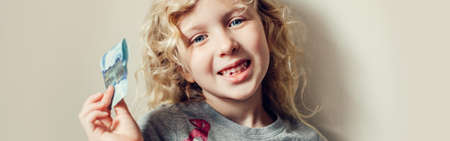 Caucasian blonde girl showing her missing tooth in a mouth and holding money from a tooth fairy. Proud child kid showing lost tooth. Growing up stage and adolescence. Web banner header.