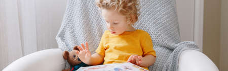 Cute baby boy toddler sitting at kids room and reading a book. Early age kid child development literacy alphabet education. Candid home authentic childhood lifestyle. Web banner header.