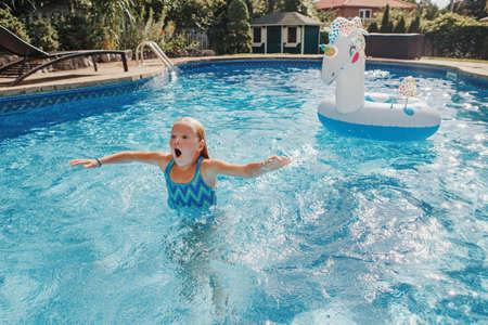 Cute funny girl swimming splashing in pool on home backyard. Kid child enjoying diving having fun in swimming pool. Summer outdoor water sport activity for kids children.