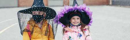 Happy Halloween. Children girls friends in witch costumes and face protective masks. People school students celebrating Halloween holiday. A new normal . Web banner header. Standard-Bild