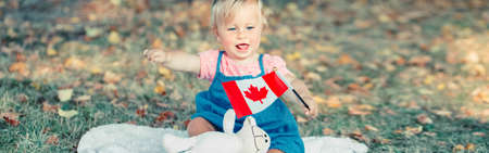 Adorable cute little Caucasian baby toddler girl waving Canadian flag in park outdoors. Kid child citizen sitting on ground in park and celebrating Canada Day on 1st of July. Web banner header. Standard-Bild