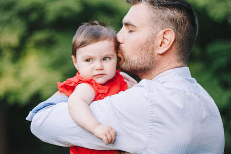 Fathers Day holiday. Middle age Caucasian proud father holding kissing baby daughter. Dad parent and daughter together in park outdoors. Life with kids children. Happy lifestyle family. Standard-Bild