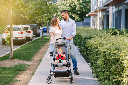 Urban life with kids children. Caucasian mother and father walking with baby daughter in stroller. Family strolling together outdoors on city street on summer day. Happy authentic lifestyle family. Standard-Bild