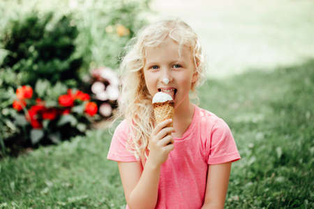 Cute funny adorable girl with long messy blonde hair eating licking ice cream from waffle cone. Child eating tasty sweet cold summer food outdoor. Summer frozen meal snack. Standard-Bild