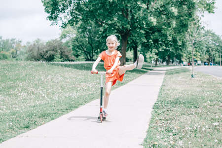 Cute funny Caucasian girl child in red orange romper riding scooter on street road park outdoor. Summer fun eco sport activity for kids children. Authentic real candid childhood lifestyle.