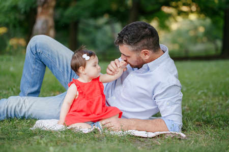 Fathers Day holiday. Middle age Caucasian proud father playing with baby daughter. Family dad and daughter sitting together outdoor in park on summer day. Parenting life with kids children. Standard-Bild