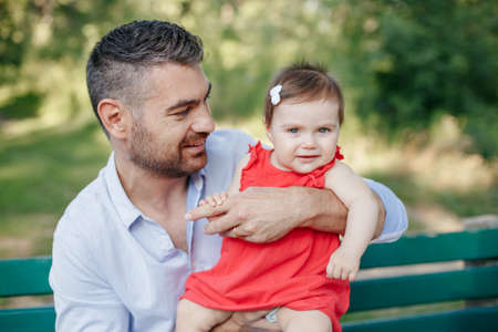 Fathers Day. Middle age Caucasian proud father playing with baby daughter. Family dad and daughter holding daughter toddler in hands outdoors in park on summer day. Life with kids children.