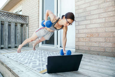 Middle age Caucasian woman doing push-ups exercises with dumb-bells on home backyard online. Video fitness sport workout on Internet. Woman learning in training class with laptop. Sport at home.