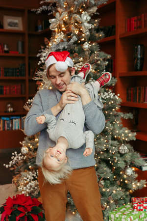 Smiling Caucasian father playing with baby girl near decorated Christmas tree. Happy family celebrating Christmas or New Year winter holiday at home. Winter holidays mood spirit.