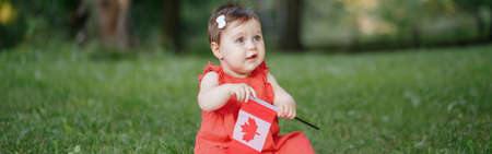 Adorable Caucasian baby toddler girl in red dress waving Canadian flag in park outdoors. Kid child citizen sitting on ground in park and celebrating Canada Day on 1st of July. Web banner header. Standard-Bild