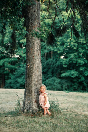 Cute smiling happy baby girl in pink dress standing by tall tree and exploring learning nature world. Small tiny kid child kid toddler in big world outdoor. Natural children curiosity.