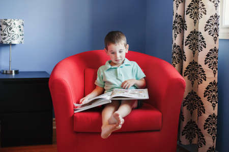 Happy Caucasian boy sitting in armchair at kids child room and reading book. Early age kid child development and literacy education. Candid home authentic childhood lifestyle concept.