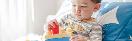 Baby toddler boy playing with learning toy stacking building blocks at home. Early age montessori education. Kids hand brain and fine motor skills development. Logic activity.  Web banner header.