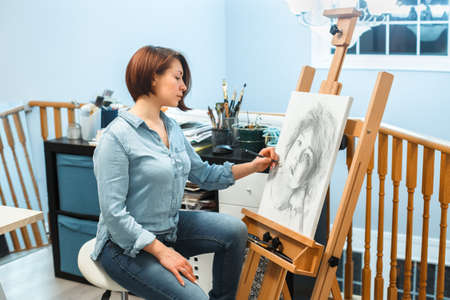 Creative hobby occupation. Caucasian woman artist drawingportrait with pencil on canvas at home art studio. Lifestyle activity hobby. Unique profession. Art freelancer doing painting.