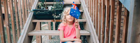 Funny Caucasian girl holding Australian flag. Child sitting on backyard at home and holding Australia flag. Kid citizen celebrating Australia Day holiday in January outdoor. Web banner header.