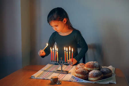 Traditional winter Jewish Hanukkah holiday. Girl lighting candles on menorah for at home. Child celebrating Chanukah festival of lights. Dreidel and Sufganiyot donuts on table. Israel Judaic holiday.