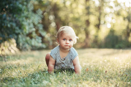Cute baby girl crawling on ground in park outdoors. Adorable child toddler learning to walk outside. Healthy physical development. Funny surprised curious kid looking at camera.
