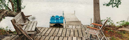 Wooden dock pier with chairs on cottage lake in Muskoka Ontario Canada. Cottage countryside rural authentic landscape nature. Travel destination in summer outdoor. Web banner header.