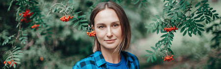 Autumn fall summer woman portrait in rowan tree berries. Closeup of pensive Caucasian middle age woman in park outdoor looking at camera. Natural beauty. Web banner header.