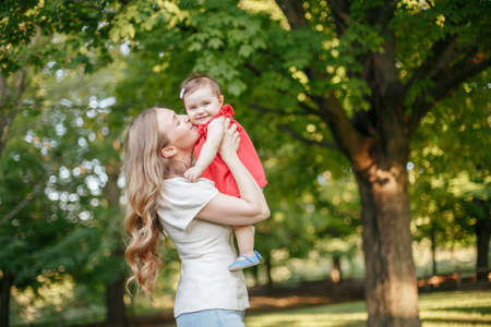 Mothers Day holiday. Young smiling Caucasian mother and girl toddler daughter hugging in park. Mom kissing child baby on summer day outdoor. Happy authentic family parenting lifestyle.