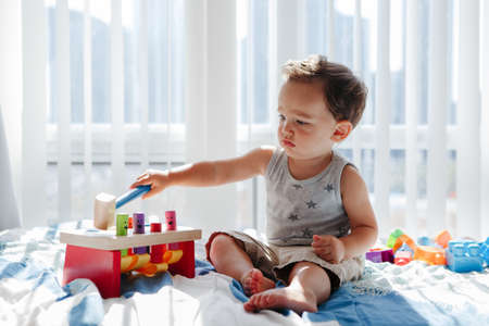 Cute baby toddler playing with learning multicolor toy pounding bench at home. Count learning.  Early age Montessori education. Kids hand brain fun development activity for preschoolers. Foto de archivo