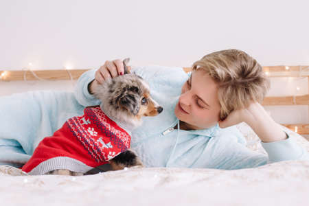 Young Caucasian woman with short hair lying on bed with cute puppy dog at home. Pet owner petting stroking little furry friend. Relationship of domestic animal and human.