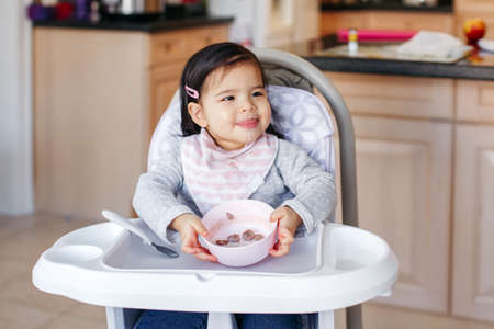 Cute adorable Asian Chinese kid girl sitting in high chair eating soup with spoon. Healthy eating for kids children. Toddler eating independently in kitchen at home. Candid real authentic moment.