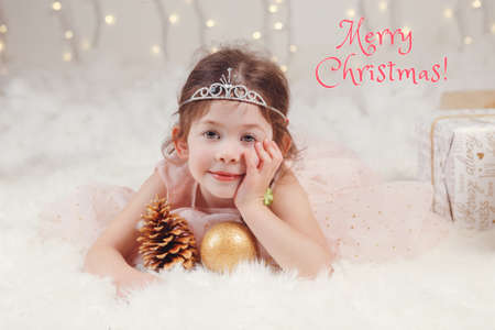 Merry Christmas. Christmas card with text. Cute adorable Caucasian girl in princess diadem crown lying on white fluffy carpet on ground. Traditional Christmas New Year holiday celebration. Foto de archivo