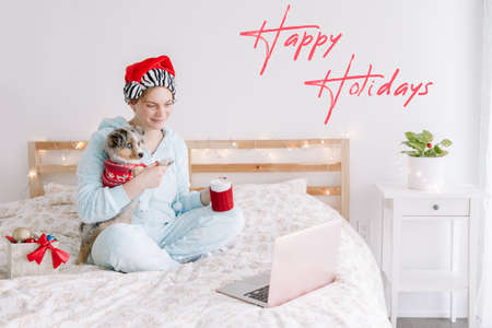 Happy holidays. Card with greeting text. Young woman in Santa hat hold cute puppy dog and call friends family in online video chat. Distant remote holiday celebration online on Internet.