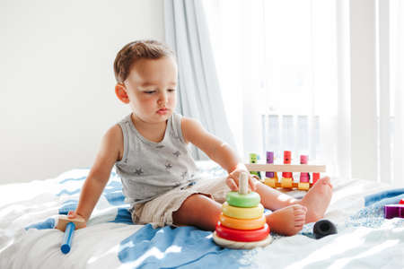 Cute baby toddler playing with learning toy pyramid stacking blocks at home. Early age Montessori education. Kids hand brain fun development activity for preschooler.