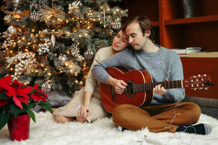 Man and woman celebrating Christmas or New Year holiday together. Man playing guitar and singing for woman. Young couple celebrating winter holidays together at home. Dating and romance.