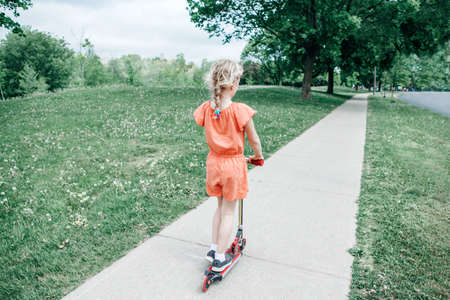 Young girl child in red orange romper riding scooter on street road park outdoor. Summer fun eco sport activity for kids children. View from back behind. Authentic real candid childhood lifestyle. Foto de archivo