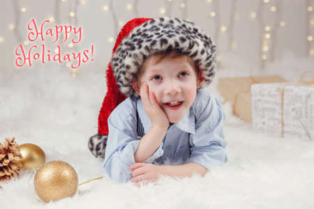 Happy holidays. Christmas card with text. Cute adorable Caucasian boy in Santa hat lying on white fluffy carpet on ground. Traditional Christmas New Year holiday celebration.