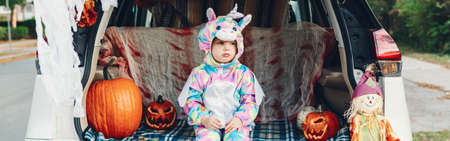 Trick or trunk. Sad upset baby in unicorn costume celebrating Halloween in trunk of car. Cute toddler celebrating October holiday outdoor. Safe alternative celebration. Web banner header.