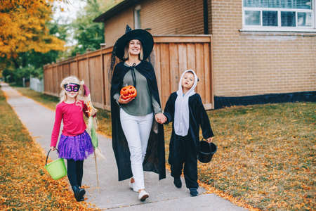 Trick or treat. Mother with children going to trick or treat on Halloween holiday. Mom with kids boy and girl in party costumes with baskets going to neighbour houses for candies and treats. Foto de archivo
