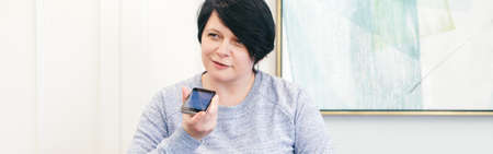 Middle age woman talking on audio chat phone with friends. New social media chat app. Speaker in live stream on smartphone. Using wireless technology. Web banner header.