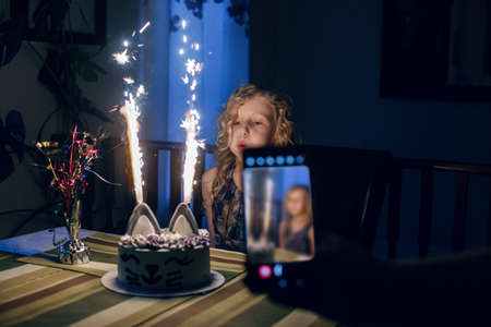 Parent taking photo of daughter blolwing candles on birthday cake. Using smartphone for taking pictures. Happy birthday party celebration at home. Making a wish while blowing candles tradition.