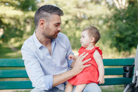 Fathers Day. Middle age Caucasian proud father talking to baby daughter. Family dad and daughter holding daughter toddler in hands outdoors in park on summer day. Life with kids children.