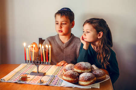 Brother and sister siblings lighting candles on menorah for Jewish Hanukkah holiday at home. Children celebrating Chanukah festival of lights. Dreidel and Sufganiyot donuts in plate on table. Foto de archivo
