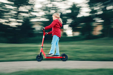 Young girl child in red jacket riding scooter on street road park outdoor. Summer fun eco sport activity for kids children. Action motion blur. Authentic real candid childhood lifestyle. Foto de archivo
