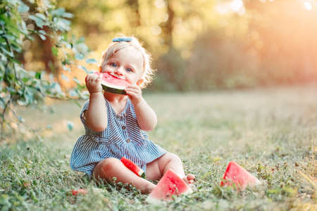 Summer seasonal picnic food. Cute Caucasian baby girl eating ripe red watermelon in park. Funny child kid sitting on ground with fresh fruit outdoors. Solid healthy finger food for toddler kids. Foto de archivo