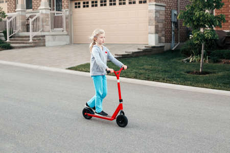 Young girl child riding red scooter on street road park outdoor. Summer fun eco sport activity hobby for kids children. Authentic real candid childhood lifestyle.