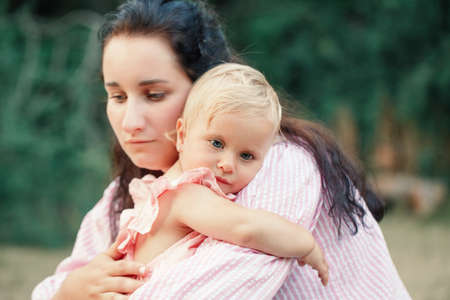 Mother hugging pacifying sad upset toddler girl. Family young mom and tired baby in park outdoor. Bonding attachment relationship of mom and child baby. Family together protection.