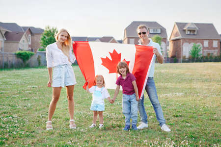 Happy Canada Day. Caucasian family with kids boy and girl standing in park and holding large Canadian flag. Parents with kids children celebrating Canada Day on 1st of July outdoor.