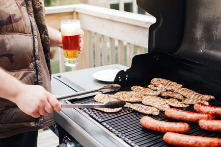 Closeup of man hand holding glass with fresh beer. Man grilling roasting meat chicken breasts and meat sausages barbeque on backyard. Chilling relaxing and cooking food on summer day on backyard. Foto de archivo