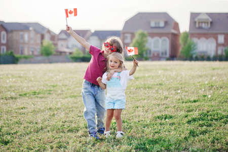 Happy Canada Day. Caucasian siblings brother and sister holding waving Canadian flag. Kids children boy and girl citizens celebrating Canada Day outdoor on 1st of July. Foto de archivo