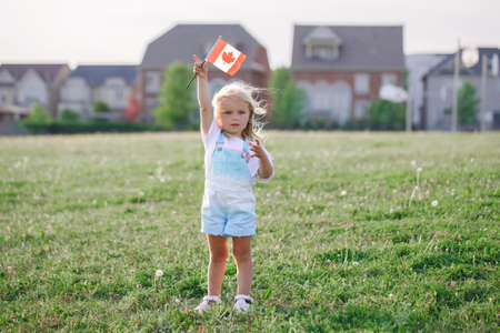 Happy Canada Day. Little blonde Caucasian toddler girl holding waving Canadian flag. Kid child citizen celebrating Canada Day outdoor on 1st of July. Foto de archivo