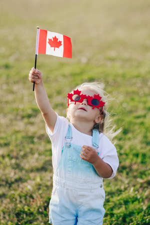 Happy Canada Day. Little Caucasian toddler girl in funny maple leaf sunglasses waving Canadian flag. Kid child citizen celebrating Canada Day outdoor on 1st of July.