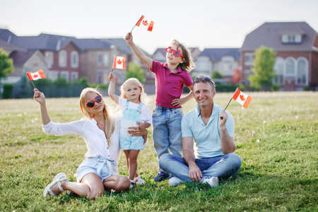 Happy Canada Day. Caucasian family with kids boy and girl sitting on ground grass in park and waving Canadian flags. Parents with kids children celebrating Canada Day on 1st of July outdoor. Foto de archivo