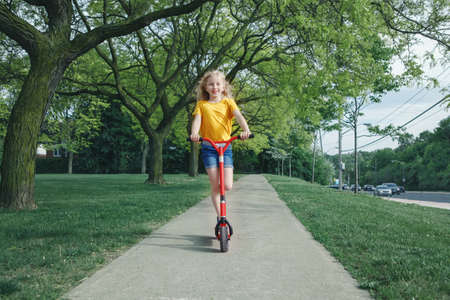 Cute funny Caucasian girl child in yellow t-shirt riding red scooter on street road park outdoor. Summer fun eco friendly sport activity for kids children. Authentic real candid childhood lifestyle.